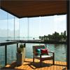 Balkonginglasning vid vattnet, ramlösa och infällbara inslagningssystem, harmoniskt uterum